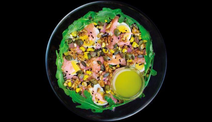 Bazë sallatë jeshile dhe spinaq, rukola, salmon i tymosur, quinoa tre ngjyrëshe, vezë të ziera, kaperi, misër, fara kungulli, arra të thërrmuara, fara susami të zeza, salcë limoni, majdanoz, vaj ulliri, kripë rozë Himalaje