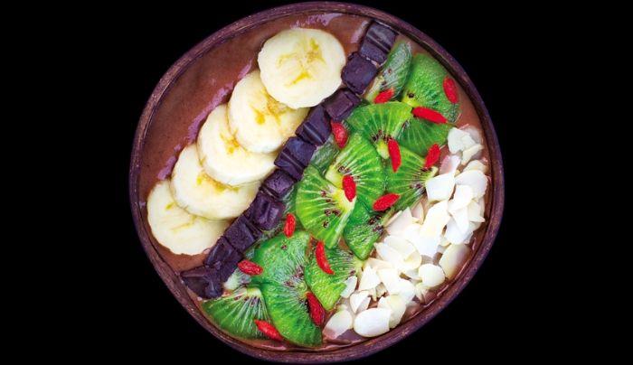 Përmbajtje e qumështit prej arrave indiane, banane dhe kakao pluhur, barishte pluhur maca, çokollatë e zezë vegane e shtëpisë me vaj kokosi, banane, kivi, mana goji, bajame të prera