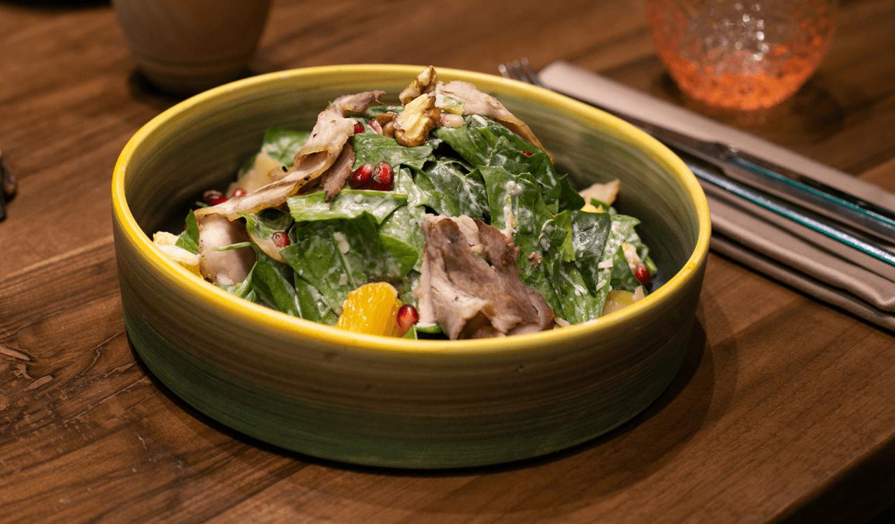Sallatë jeshile, salcë Caesar, kotoletë pule, bukë e thekur, misër, parmixhano
