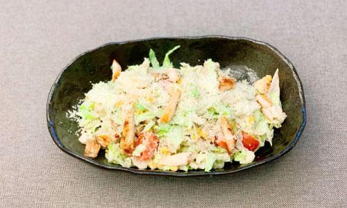 Sallatë ajsberg, pulë, misër, pomodorini, djathë grana dhe bukë e thekur