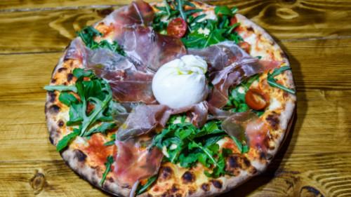 Salcë domate, proshutë krudo, pomodorini, rukola, burrata e freskët. Pizza bëhet me brumë pa maja në furrë druri