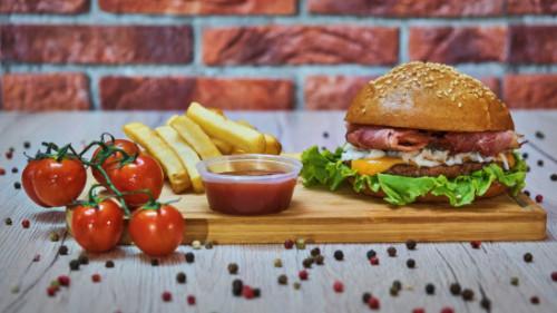Burger 100 përqind mish viçi vendi, panine shtëpie me susam, sallatë jeshile, chedar, mocarela pice, bacon, salcë e shtëpisë me BBQ dhe mjaltë, shoqëruar me patate dhe ketchup