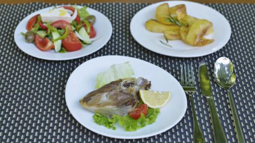 Mish qingji i furrës. patate të furrës dhe sallatë greke