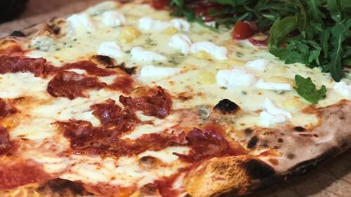 Salcë domate, mocarela fiore di latte, pomodorini, proshutë krudo, rukola, grana, sallam pikant, 4 lloje djathi, rikota. Pizza bëhet me brumë pa maja në furrë druri.