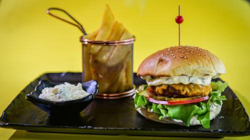 Buka jonë, hamburger viçi ose pule me djathë cedar, salcë e freskët, sallatë, kastravec turshi, patate, domate