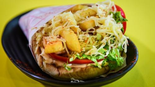 Pita jonë, sos, domate, sallatë, lakër e bardhë me karrota të marinuara, patate, djathë guda