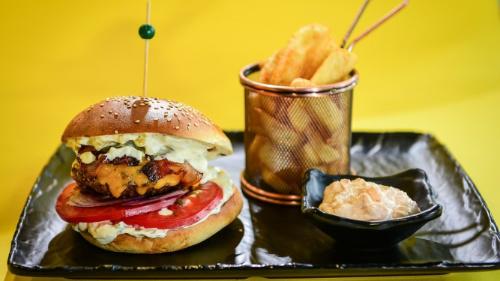 Buka jonë, hamburger viçi ose pule me djathë cedar, beikon, lakër e kuqe e marinuar, salcë e freskët, qepë e kuqe, domate, patate