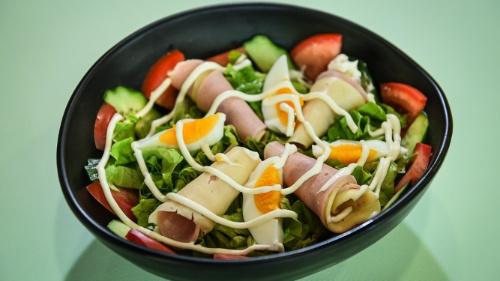 Sallatë jeshile, domate, kastravec, djathë, proshutë, vezë, sos