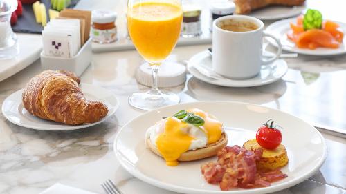 Eggs benedict, salmon të tymosur, fruta, croissant, lëng portokalli, kafe