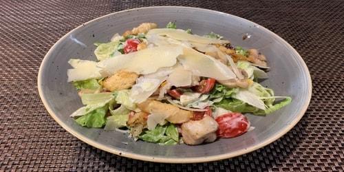 Sallatë iceberg, pomodorini, misër, fileto pule, bukë krokante, grana dhe salcë ceasar