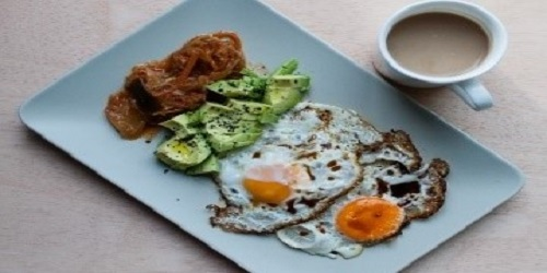 Eggs with bacon and avocado, served with baked fritter and tomato slices.